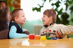 Relatie tussen jonge geitjes gehandicapt in kleuterschool stock afbeelding