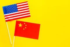 Relaties V.S.-China De samenwerking van het land Amerikaanse en Chinese vlaggen op de gele ruimte van het achtergrond hoogste men Stock Afbeelding