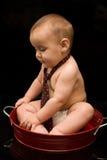Relation étroite s'usante de bébé adorable dans le carter rouge photos stock