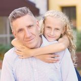 Relations. Dad. Daughter. Heat. Family. Love. Gentle embrace. Relations. Dad and daughter. Happy family. Gentle embrace. Blurred background Royalty Free Stock Photo