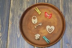 Composition on ceramic dish. Stylized heart, lock with key, decorative butterfly, satin flower and clothespins. Dark natural stock photography