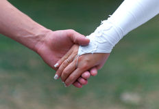 Relationship. Newlywedses to hold for hand, walking on park Stock Photography