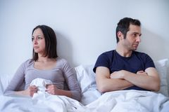 Sad couple and relationship difficulties in bed stock photography