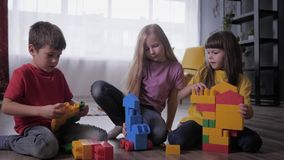 Relationship of children, charming girlfriends and a cute boy together play educational toys with colorful blocks during