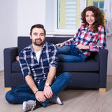Relationship concept - beautiful couple sitting on sofa in new f Royalty Free Stock Photos