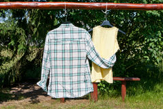 Relationship concept. Two pieces of clothing hanging outdoors and hugging. Love concept Stock Photo