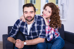 Relationship concept - young beautiful couple sitting on sofa Stock Photography
