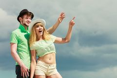 Young couple looking up showing with finger outdoor Stock Photos
