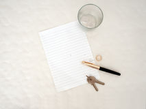 Relationship ends. Breakup, divorce concept. Lined blank paper. Objects include pen, keys and wedding ring on tear stained paper. Blank page for your message stock photo