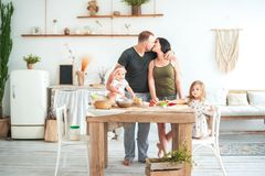 Relationship in the family with small children. Dad and mom kiss in the bright kitchen, children cook in the kitchen stock photography