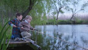 Relationship, friendly boy brothers catch fish on a wooden fishing rod sitting on the boards by the pond in the middle