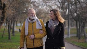Relationship granddaughter and grandfather, an elderly man with a gray beard walking with a girl in park in the autumn