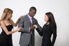 Relationship Issues. Two young women and one adult man on a white background. It looks as if he might be trying to chose between to the two Royalty Free Stock Images