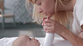 Relationship mother and child, parent kisses little hands of her adorable baby daughter who lies on changing table close stock footage