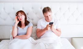 Relationship problems concept - a middle-aged couple lying in bed in the morning a man holding a smartphone. Middle age couple in stock images