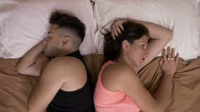 Relationship problems with couple lovers in bed standing back to back feeling guilt and remorse after arguing and fighting. Relationship problems with young stock footage