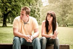 Relationship problems - couple in park. Young couple sitting outdoors on bench having relationship problems Stock Images