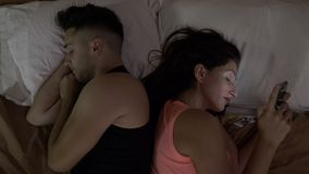 Relationship problems with man comforting his woman in bed addicted to her smartphone on social media stock footage