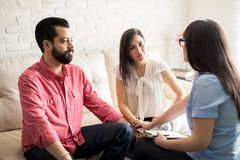 Marriage counselor mediating couple thinking about divorce. Relationship psychologist mediating couple thinking about divorce. Hispanic couple with problem in Stock Photography