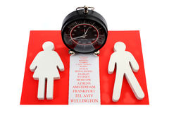 Relationship and travel. Wooden male and female figure with cities names between them and terminal clock above them stock photos