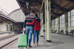 Relationship and travelling concept. Lovely woman and man cuddle while walk across railway station platform, carry suitcase, royalty free stock images