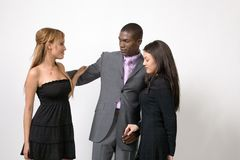 Relationship Trouble. A adult man in a suit with two young women, one on each side of him. It looks like he is trying to choose between the two Royalty Free Stock Images