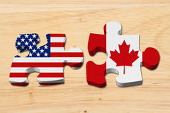 Relationship between the USA and Canada. Two puzzle pieces with the flags of USA and Canada on wood royalty free stock photography