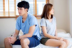 Relationship of young asian couple having problem on bed in the bedroom at home, family having conflict argument with unhappy. Men and women with issue stock photo