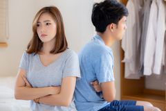 Relationship of young asian couple having problem on bed in the bedroom at home, family having conflict argument with unhappy. Men and women with issue royalty free stock photos