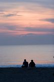 Relationships. Couple On tropical beach watching sunset Stock Image