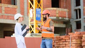 Relationships between construction clients and participants of building industry. Construction team communication. Concept. Woman engineer and brutal builder royalty free stock image