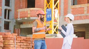 Relationships between construction clients and participants of building industry. Construction team communication. Concept. Woman engineer and brutal builder royalty free stock images