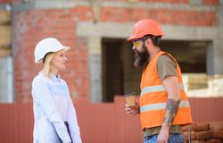 Relationships between construction clients and participants of building industry. Woman engineer and brutal builder. Communicate construction site background stock photography