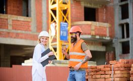 Relationships between construction clients and participants building industry. Woman engineer and brutal builder. Communicate construction site background stock images