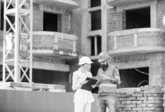 Relationships between construction clients and participants building industry. Woman engineer and builder communicate at. Construction site. Discussing plan stock image