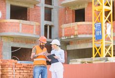 Relationships between construction clients and participants building industry. Woman engineer and builder communicate at. Construction site. Discussing plan royalty free stock image