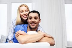 Happy couple sitting on sofa and hugging at home stock images