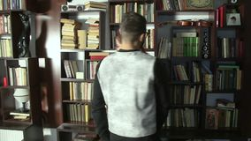 Man and young girl choosing a book to read. Two people looking for books in library. Students searching for information. Relationships of young people in the stock video