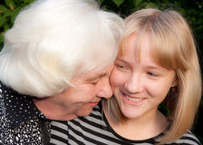 Relatives. The grand daughter and the grandmother smile to the photographer Stock Image