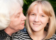 Relatives. The grand daughter and the grandmother smile to the photographer Stock Images