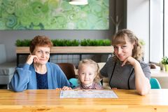 Cheerful friendly family of three women. Relatives celebrate a holiday in a cafe stock photography