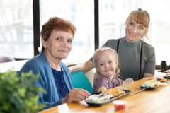Cheerful friendly family of three women. Relatives celebrate a holiday in a cafe, sit on the background of a large window stock image