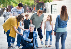 Relatives near grandfather who filling ache in heart. Relatives standing near grandfather who filling ache in a heart Royalty Free Stock Photos