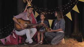 Relatives on picnic, mom dad and baby eat during nights rest in forest against wigwam. Relatives on picnic, mom dad and baby eat during a nights rest in the stock video footage