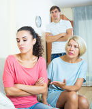 Relatives quarrelling with young woman in domestic interior Stock Photos