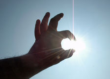 Relativity. Hand grabbing sun - relativity metaphor of point of view - backlit Royalty Free Stock Image