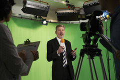 Relatore maschio In Television Studio con la squadra in priorità alta Fotografia Stock