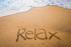 Relax被写入沙子在海滩 免版税库存照片