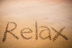 Relax écrite dans le sable sur une plage Photographie stock libre de droits