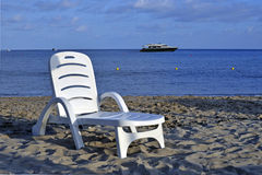 Relax. Deckchair on the shoreline with anchored yacht onshore Stock Photography